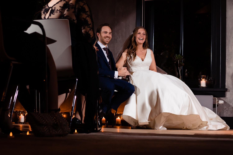 Bruidspaar zit hand in hand bij de ceremonie