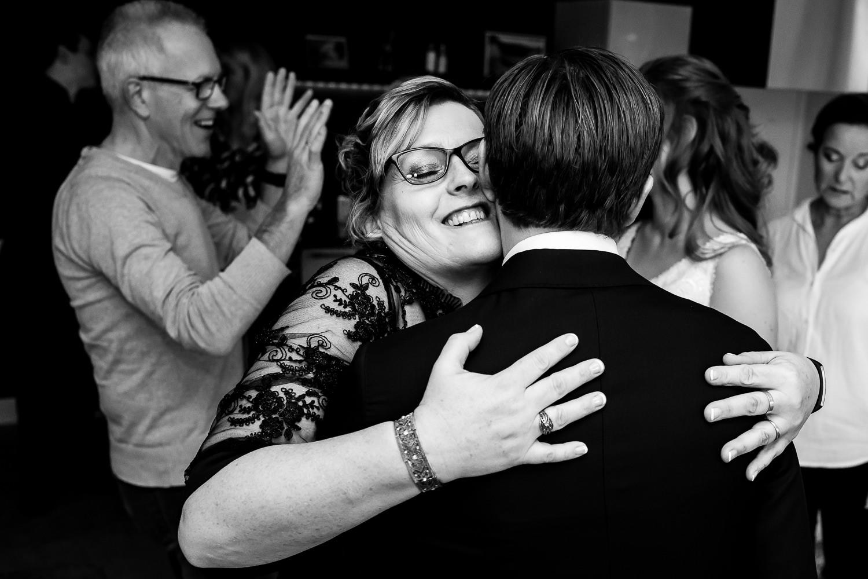 Zwart wit foto van een moeder die haar schoonzoon omhelst