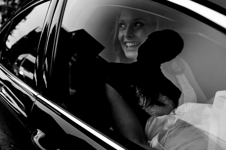 Zwart wit foto van de bruid vanachter het glas van de trouwauto