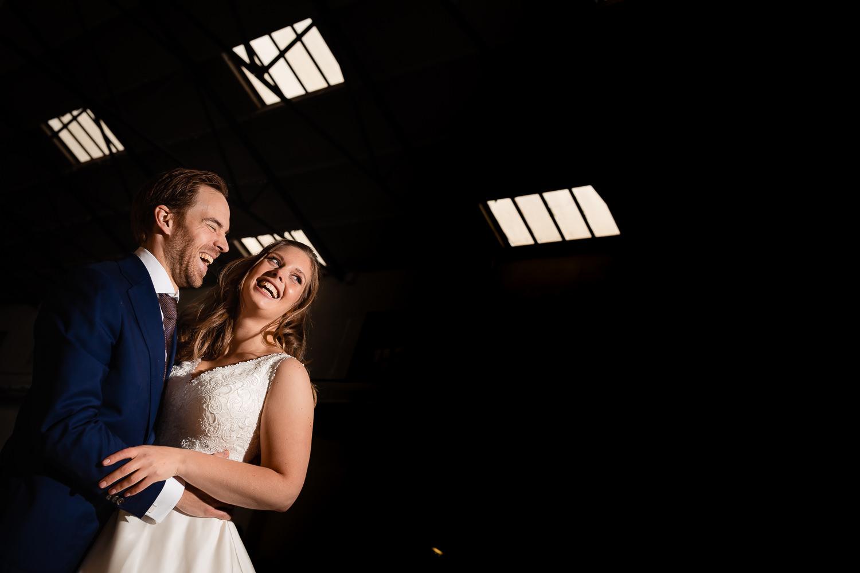 Lachend bruidspaar met een donkere achtergrond