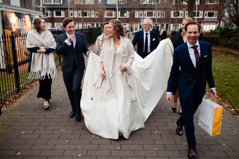 Bruidspaar loopt door de stad terwijl familie en vrienden de sleep omhoog houden
