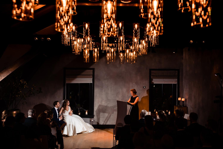 Bruidspaar luistert toe terwijl één van de gasten een speech houdt achter een lessenaar