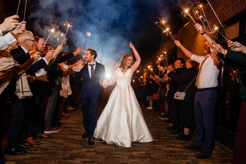Bruidspaar loopt zwaaiend en lachend door boog van gasten door die sterretjes vasthouden