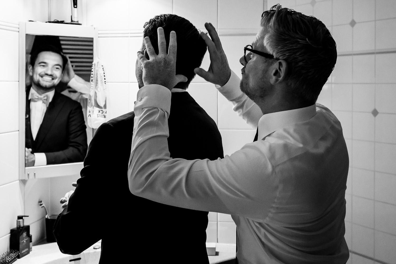 Zwart wit foto van een vader die het haar van de bruidegom netjes doet, bruidegom kijkt in de spiegel