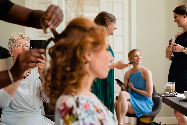 Terwijl de visagist het haar van de bruid doet zijn de vriendinnen druk bezig met hun telefoon