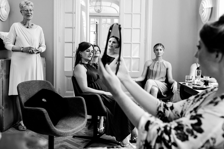 Zwart wit foto van een bruid die haar make-up bekijkt in de spiegel terwijl haar vriendinnen en moeder toekijken
