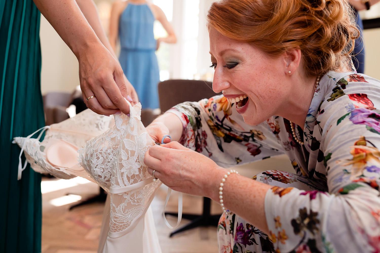 Bruid die lachend een overbodig touwtje van haar trouwjurk afknipt
