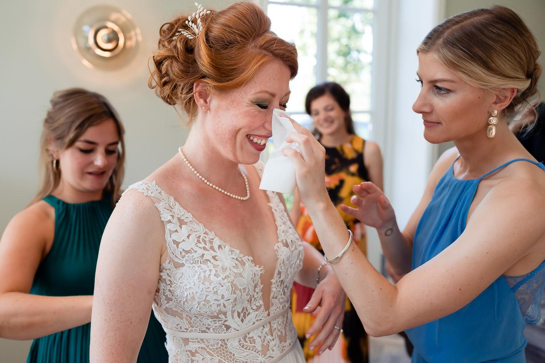 Vriendin veegt een traan weg met een zakdoekje bij emotionele bruid