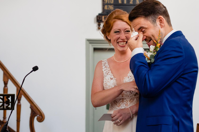 Lachend bruidspaar terwijl hij in zijn ogen veegt