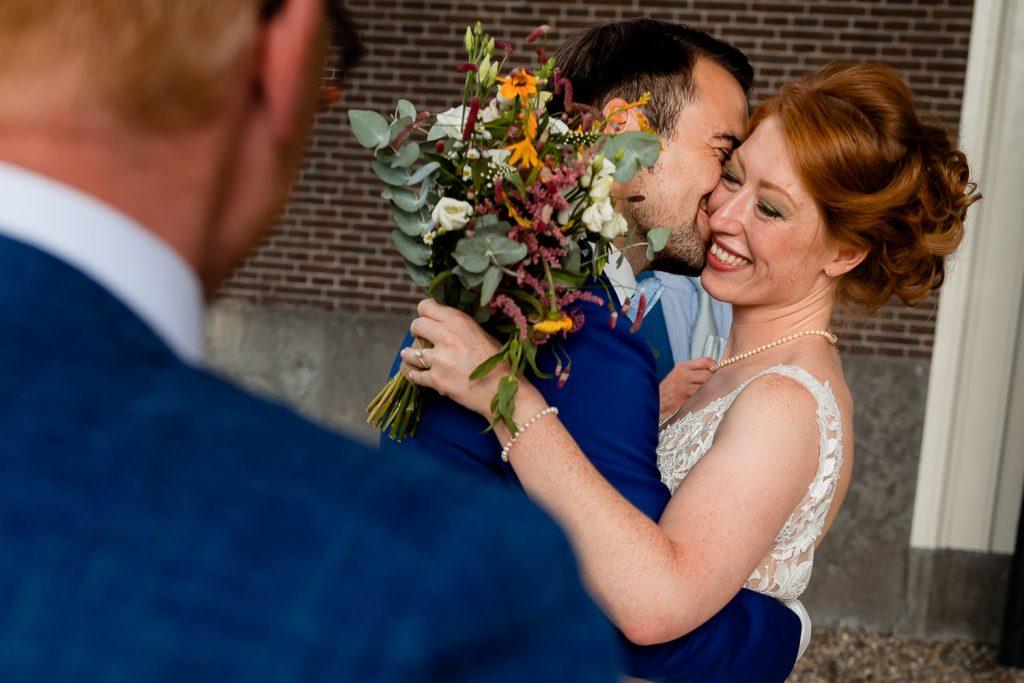 Bruidegom kust de bruid lachend met een bruidsboeket op de voorgrond