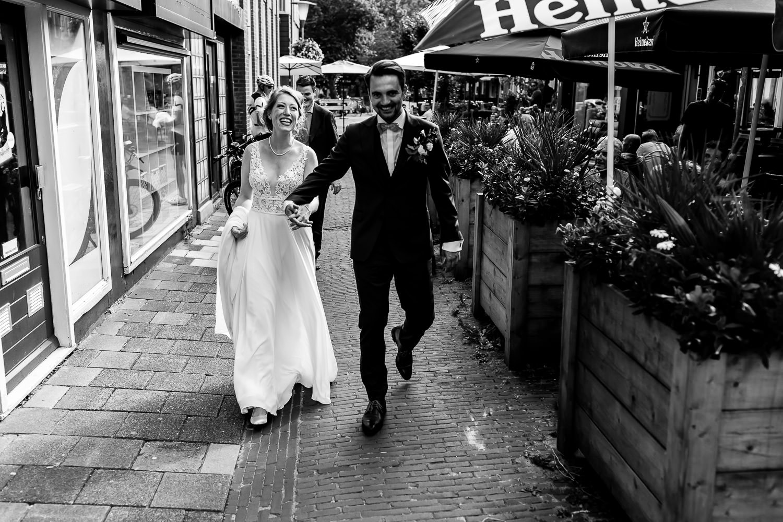 Zwart wit foto van een bruidspaar dat door de straatje van een stad loopt