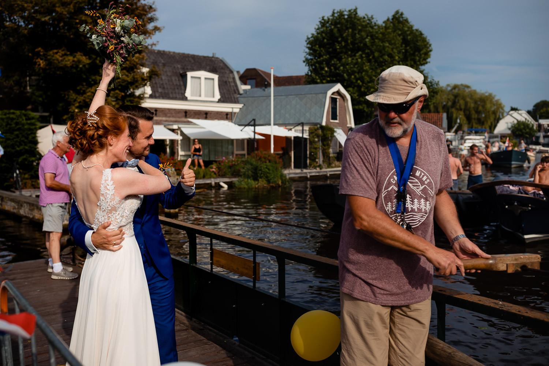 Bruidspaar zwaait naar mensen op het water