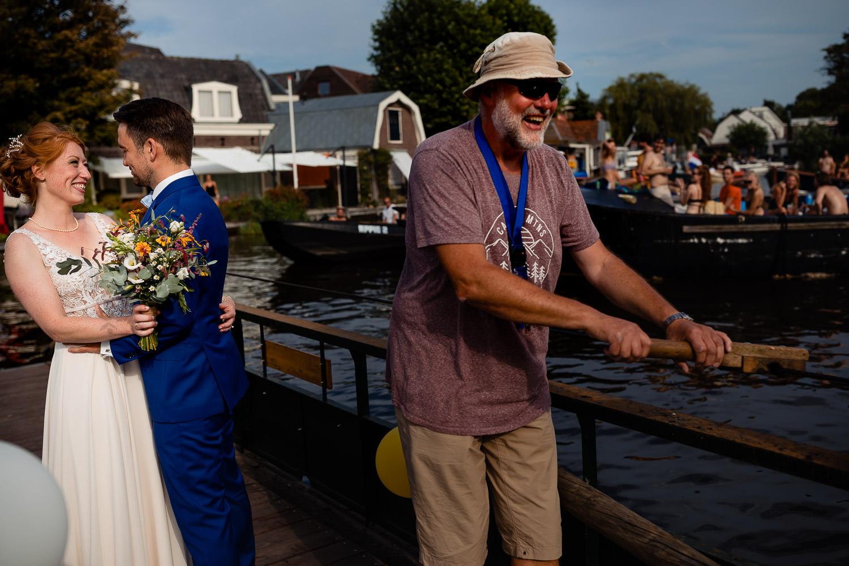 Bruidspaar kijkt lachend naar elkaar met een bootje met mensen op de achtergrond