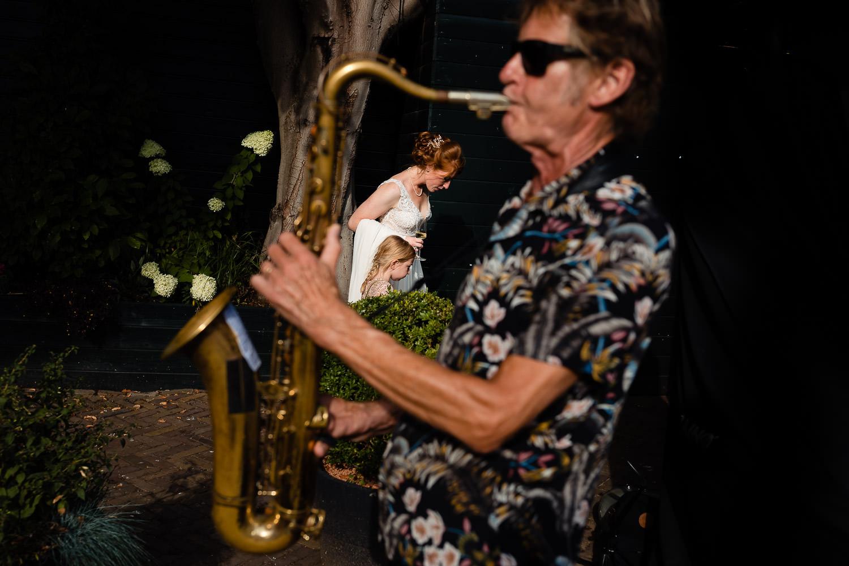 Vrouw speelt trompet met de bruid op de achtergrond met een glas wijn in haar hand