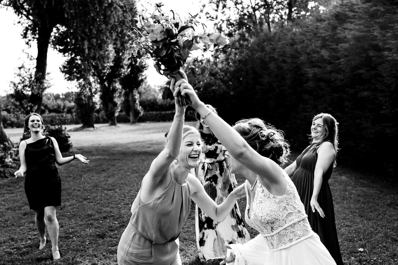 Zwart wit foto van vriendin die lachend bruidsboeket pakt voordat ze het de groep in kan gooien