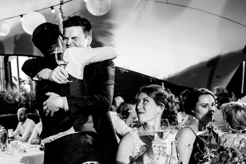 Zwart wit foto van bruidegom die emotioneel zijn vriend omhelst
