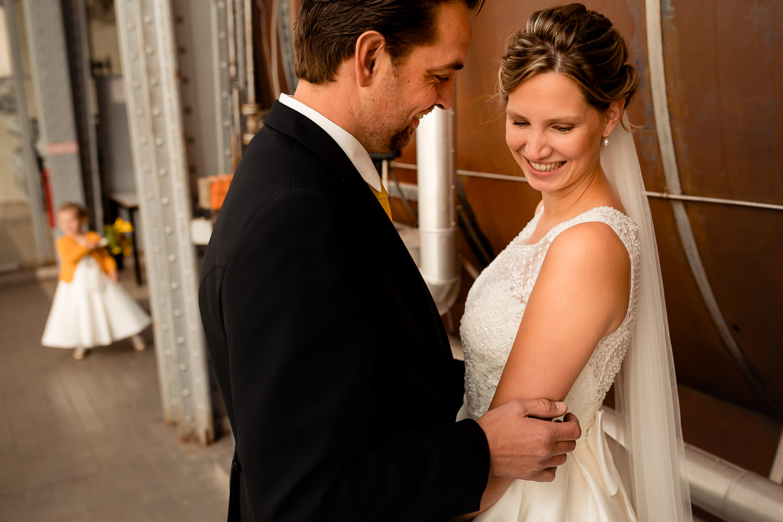 Close-up van een bruidspaar met een klein bruidsmeisje op de achtergrond