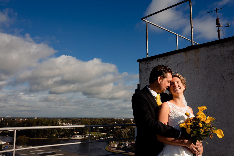 Bruidspaar poseert met een ver uitzicht over het water
