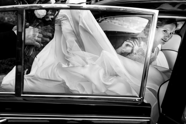 Zwart wit foto van een bruid die probeert in de auto te gaan met haar lange sleep