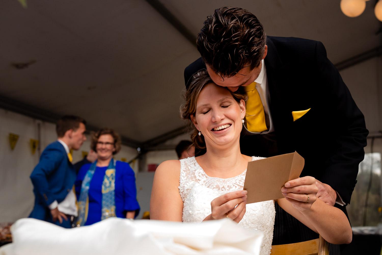 Emotionele bruid met de bruidegom die een kaart leest