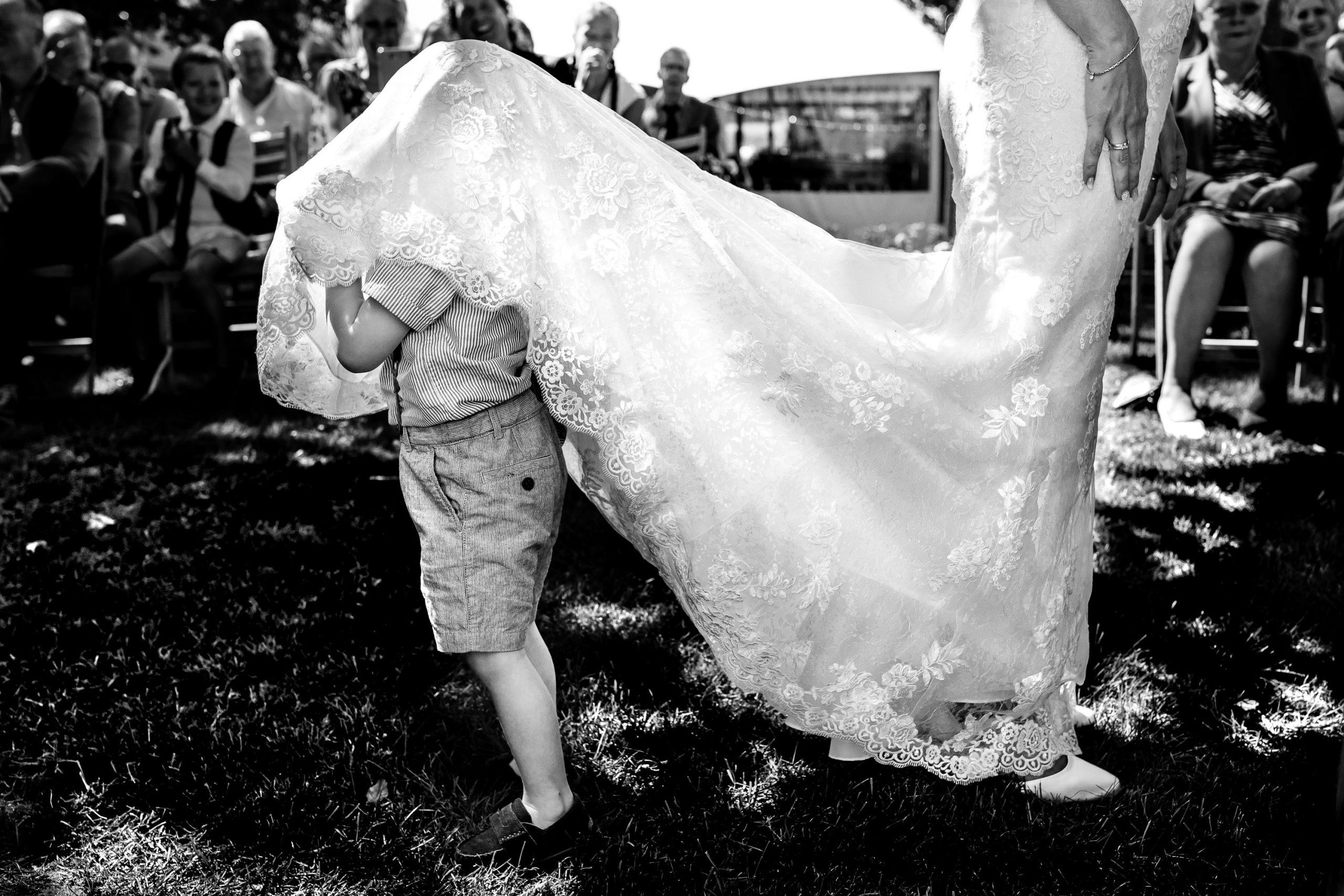 Zwart wit foto van klein jongetje dat zich verstopt onder de trouwjurk van de bruid