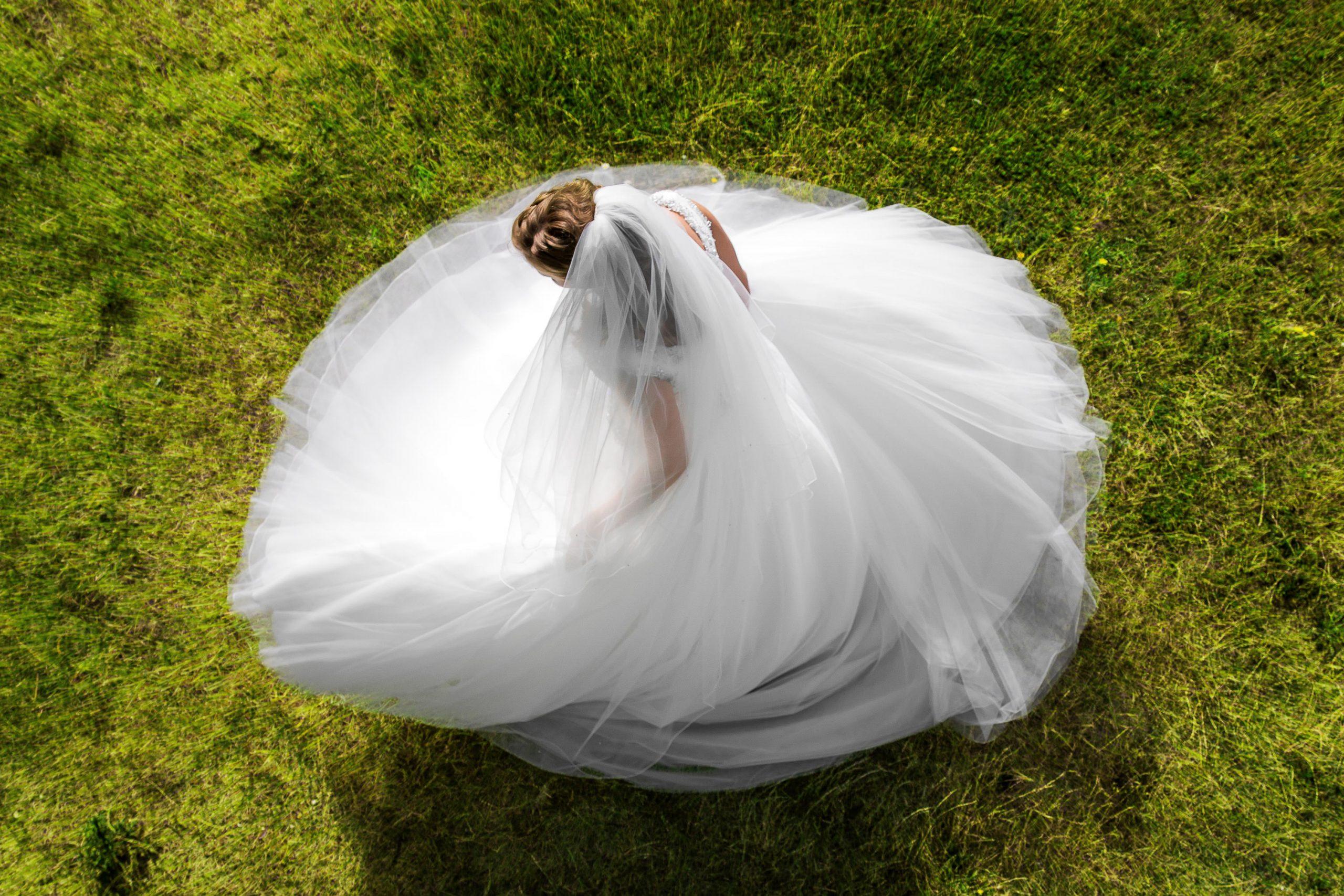 Foto van bovenaf genomen van een bruid die rond draait met haar trouwjurk