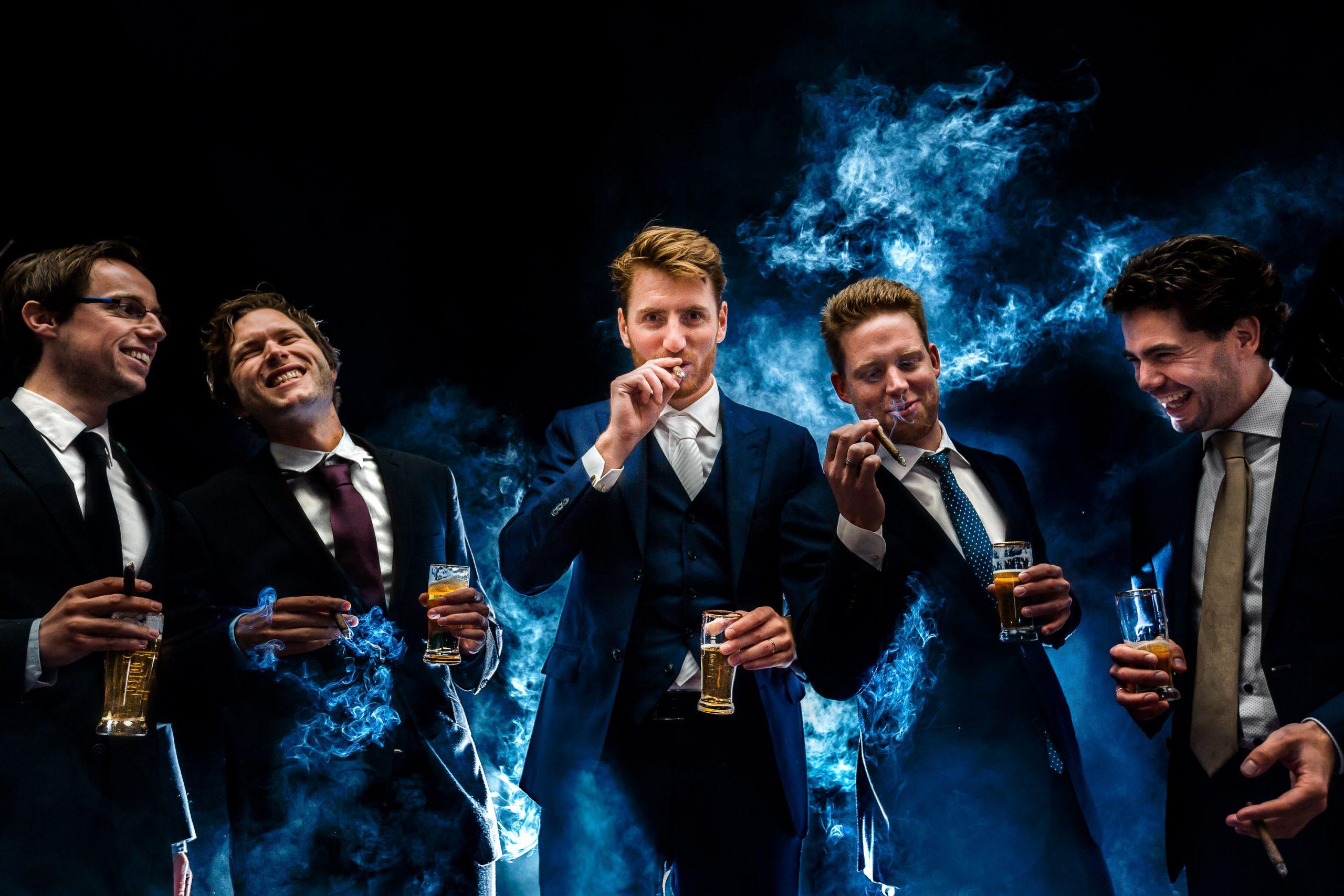Bruidegom staat samen met zijn vrienden een sigaar te roken met rook op de achtergrond
