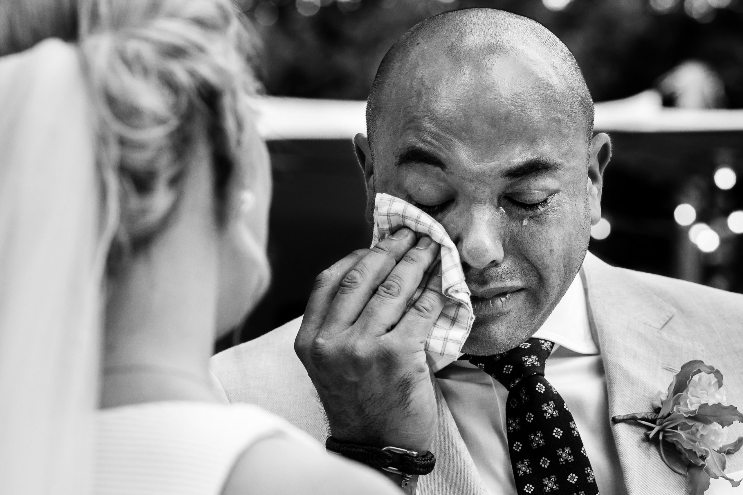 Zwart wit foto van een close-up van een bruidegom die zijn tranen wegveegt