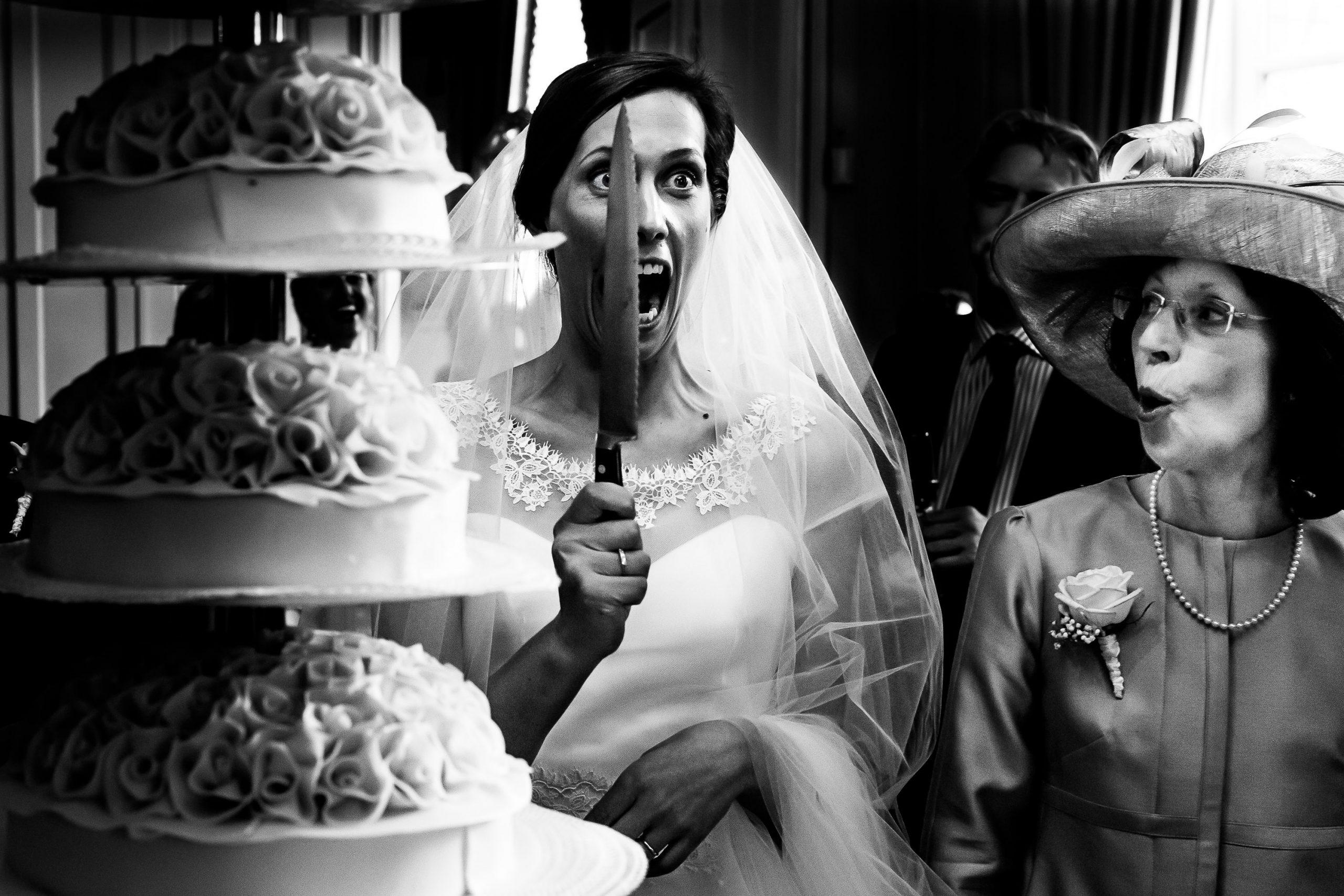 Zwart wit foto van een bruid die lachend met een mes voor haar gezicht staat terwijl haar moeder verbaasd lachend toekijkt