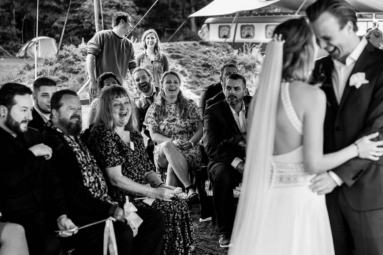 Zwart wit foto van lachend bruidspaar en familie tijdens de ceremonie