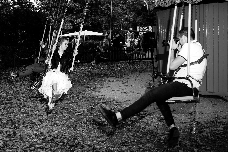 Zwart wit foto van de bruidsfotograaf die het bruidspaar fotografeert op een draaimolen