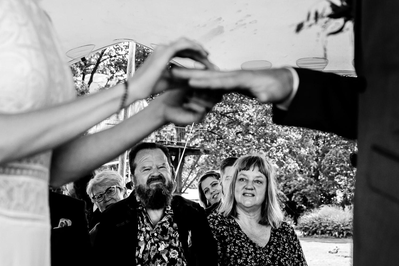 Zwart wit foto van de handen van het bruidspaar terwijl ze de ringen omdoen en familie kijkt toe