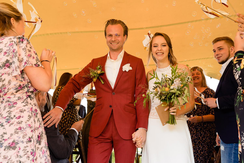 Bruidspaar loopt lachend terug na de ceremonie en bruidegom geeft één van de gasten een schouderklopje