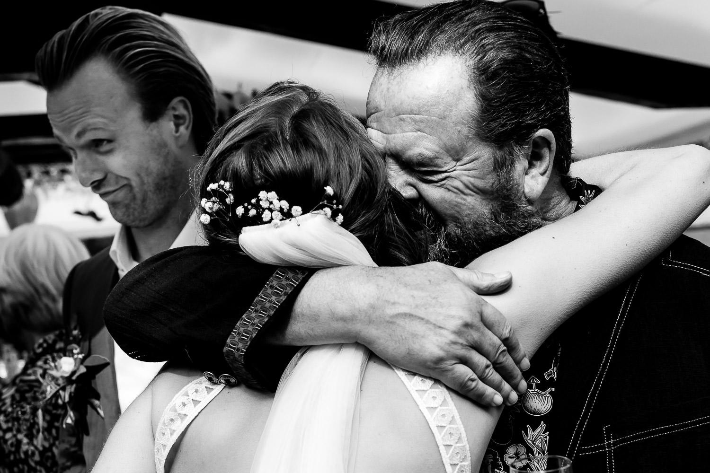 Zwart wit foto van een vader die zijn dochter omhelst bij de first-look
