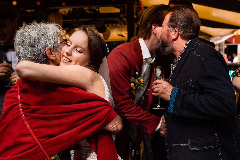 Bruidspaar wordt omhelst en gefeliciteerd door hun ouders