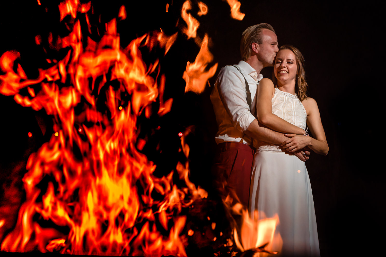 Bruidspaar dat elkaar kust en een kampvuur op de voorgrond