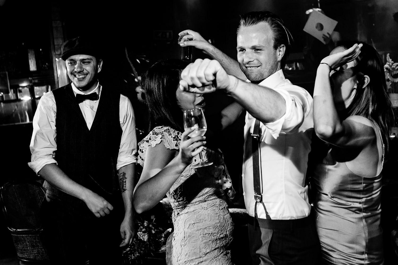 Zwart wit foto van bruidegom die danst met een vrouw met een glas wijn