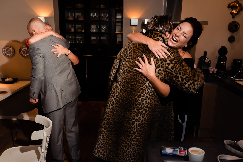 Lachende bruid die haar moeder omhelst voordat ze haar trouwjurk aan gaat trekken