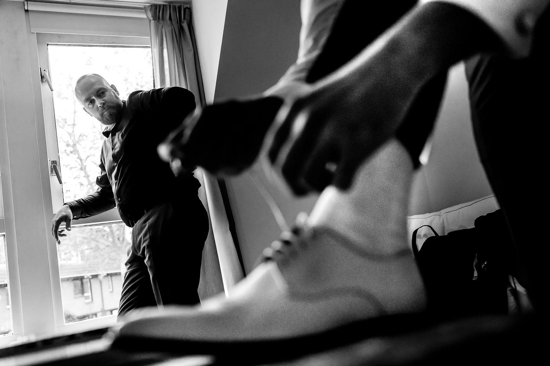 Zwart wit foto van de bruidegom die zijn schoenen aandoet terwijl zijn vader toekijkt