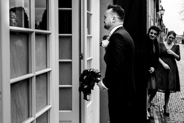 Zwart wit foto van de first-look, de bruidegom is emotioneel