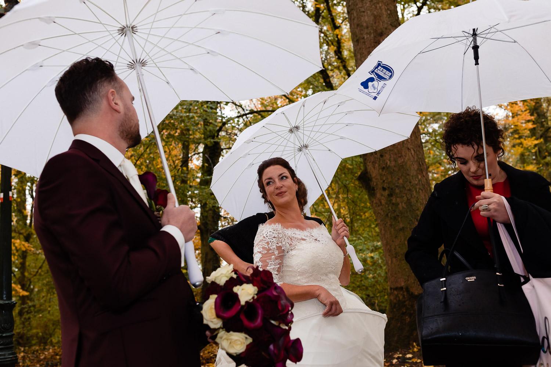 Bruid en bruidegom dragen beide een paraplu en kijken elkaar aan