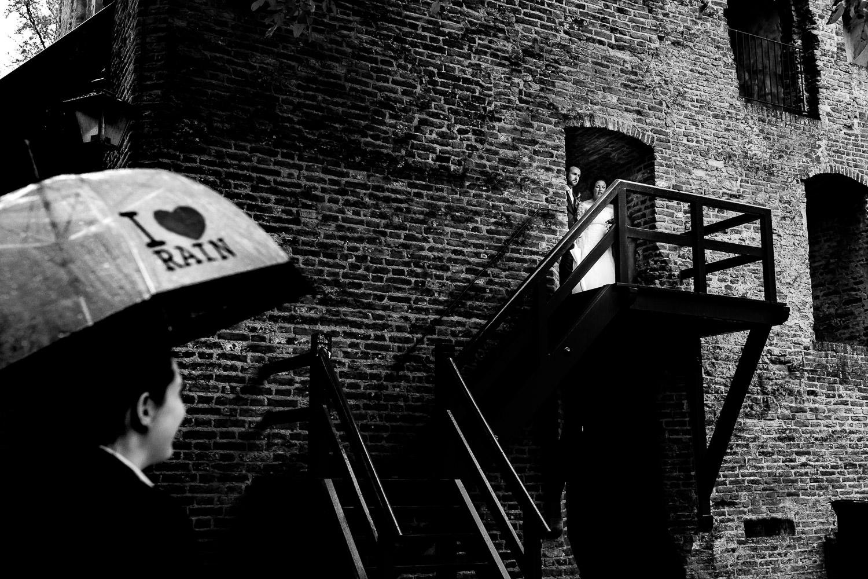 Zwart wit foto van bruidspaar dat naar buiten komt lopen bij een trap
