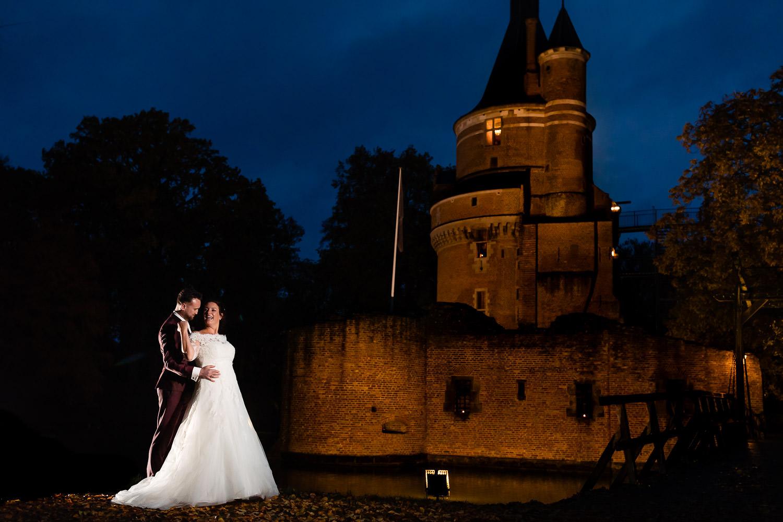 Bruidspaar poseert met een verlicht kasteel op de achtergrond