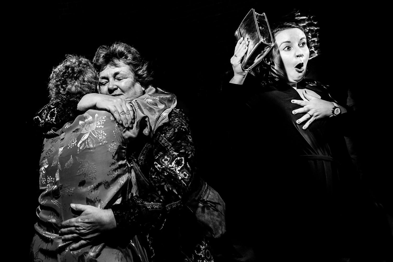 Zwart wit foto van twee oudere vrouwen elkaar omhelzen met een dansende vrouw naast hen
