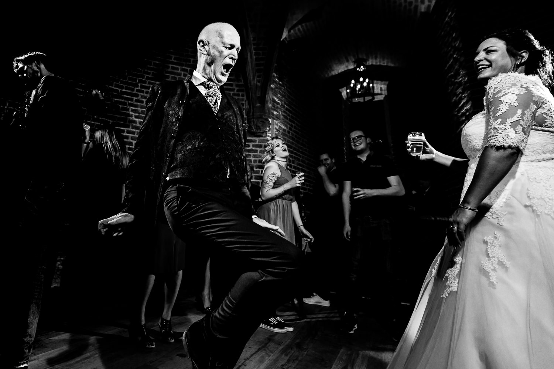 Zwart wit foto van een dansende bruid met dansende (schoon)vader