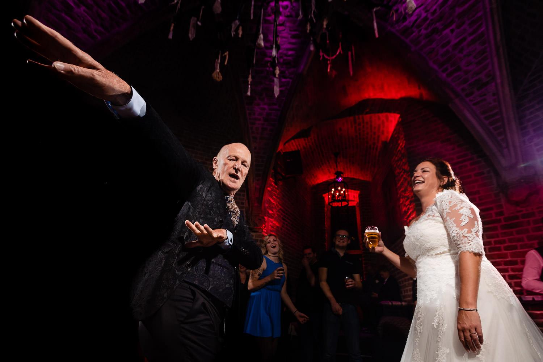 Bruid lacht terwijl haar (schoon)vader een gekke dansmove doet