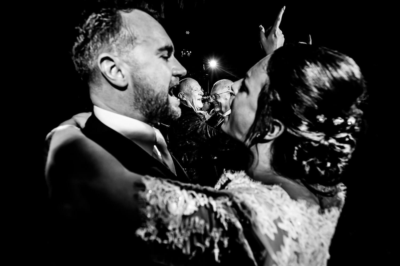 Zwart wit foto van een dansend bruidspaar met dansende mensen op de achtergrond