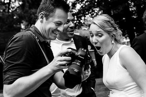Bruid kijkt verbaasd achter op de camera bij fotograaf
