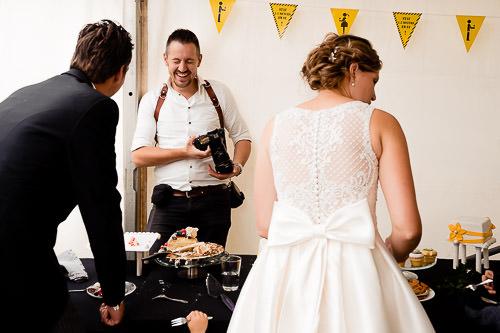 Bruidspaar pakt eten en fotograaf lacht hierbij