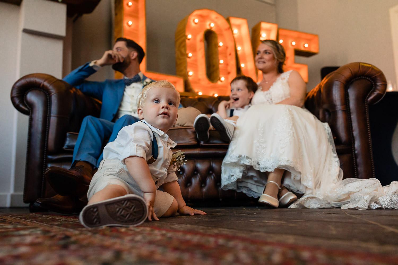 Bruidspaar zit op een bank met twee kleine jongetjes waarvan er één op de grond zit